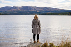 Alone thinking woman standing on a stone. And looking out over a beautiful mountain landscape Stock Images