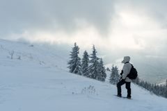 Alone tourist with a backpack. In the high mountains in winter time. Travel concept Royalty Free Stock Photo