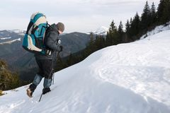 Alone tourist with a backpack. In the high mountains in winter time. Travel concept Stock Photo
