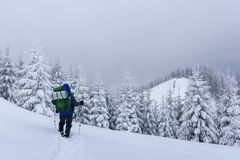 Alone tourist with a backpack. In the high mountains in winter time. Travel concept Royalty Free Stock Photography