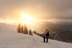 Alone tourist with a backpack. In the high mountains in winter time. Travel concept Stock Images