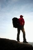 Alone tourist with big backpack stand on cliff edge  and watching into deep valley bellow. Stock Images