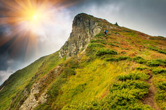 Alone tourist climbing to the top. Summer mountain landscape in the sunlight. Alone tourist climbing to the top Stock Photography