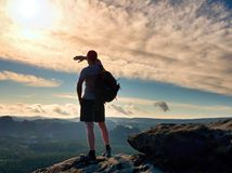 Alone tourist with sporty backpack stand on cliff edge and watching into deep valley bellow. Royalty Free Stock Image