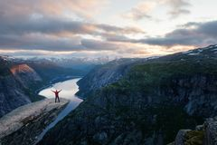 Alone tourist on Trolltunga rock. Most spectacular and famous scenic cliff in Norway royalty free stock image