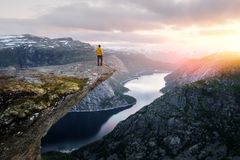Alone tourist on Trolltunga rock. Most spectacular and famous scenic cliff in Norway stock photography