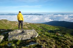 Alone tourist in yellow jacket. Stay on rock on high mountains royalty free stock photos