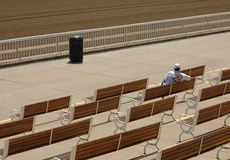 Alone at the track. Man sitting alone at race track Stock Photography