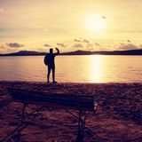 Alone traveler with backpack. Man  on sea beach at wooden bench, cold sunny autumn evening Royalty Free Stock Photography