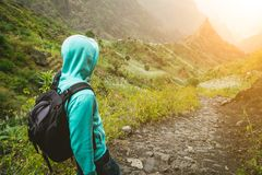 Alone traveler with backpack walking down cobbled trekking trail towards green valley. Sun flares on hoziron. Santo. Antao Island, Cape Verde Stock Photo