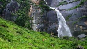 Alone trekker weared in red jacket near the Jogini waterfall, Manali, Himachal Pradesh, India stock footage