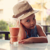 Alone unhappy kid girl sitting in restaurant and does not want t. O drink healthy juice on summer background Stock Photography