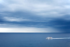 Alone white boat on sea and stormy sky Royalty Free Stock Images