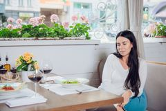 Alone woman in cafe, sad beautiful girl. Attractive bored woman in restaurant. Beautiful young woman dining at restaurant. beloved man did not come on a date Royalty Free Stock Photography
