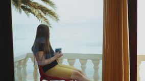 Alone woman is drinking coffee or tea in morning on balcony with blue sea view, point of view from window, rapid video