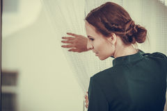 Alone woman looking through window waiting Royalty Free Stock Photo