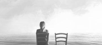 Sad woman sitting next to her lover`s empty chair Royalty Free Stock Images