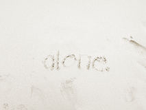 Alone. The word alone is handwritten on a clean beach Royalty Free Stock Image