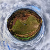 Alone in the world. Panoramic 360 degree image taken from above a man sitting on a bench on the Malvern Hills Worcestershire UK Stock Image