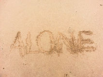 Alone written on sand by sea Royalty Free Stock Images