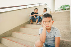 Alone. Young asian boy sitting alone royalty free stock images
