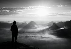 Alone young girl tourist feast autumn  daybreak on the sharp corner of sandstone rock and watch over misty valley to Sun. Royalty Free Stock Photo