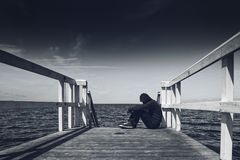 Alone Young Man at the Edge of Wooden Pier Stock Photo