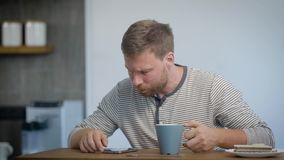 Alone young man is having breakfast in his apartment, sitting on kitchen, drinking coffee and looking on a display of. Smartphone, browsing by mobile internet stock footage