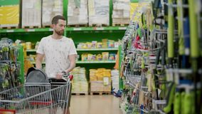 Alone young man is walking in sales hall in shop, rolling trolley in front stock footage