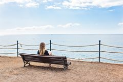 Alone young woman sitting on the bench Stock Photos