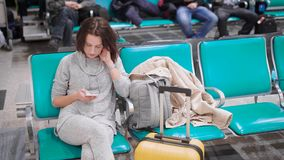 Alone young woman is sitting on a chair in departure lounge of airport before flight, reading messages in her mobile. Other passengers are sitting behind stock video