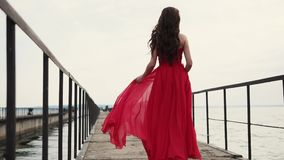 Lonely romantic woman is walking on old empty pier of sea in daytime, back view