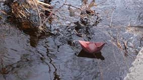 Along the bank river brown paper boat sails in clear water . Along bank river brown paper boat sails in clear water stock video footage