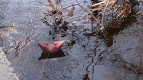 Along the bank river brown paper boat sails in clear water . Along bank river brown paper boat sails in clear water stock video