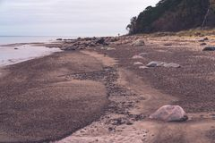 Along the beach there are bigger and smaller stones. The sandy coast and horizon of the Baltic Sea; the sea is calm, without waves; along the beach there are royalty free stock photo
