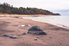 Along the beach there are bigger and smaller stones. The sandy coast and horizon of the Baltic Sea; the sea is calm, without waves; along the beach there are royalty free stock photography