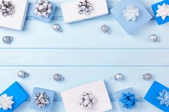 Along the edges of the light blue background, blue and white gift boxes and Christmas silver balls are laid out. Empty. Place for text and inscriptions, copy stock photo