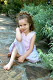 Along a Garden Pathway. Young girl props her elbow on her knee.  She is sitting in the middle of a garden on a stone pathway.  She has on a sleeveless pink dress Royalty Free Stock Image