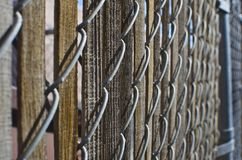 ALong the old wooden chain linked fence. Along the old steel and wooden metal chain linked fence in the back warehouse area by the cans stock image