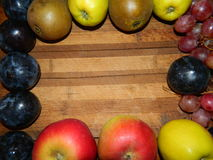 Along the perimeter of the wooden planks laid out plums, pears, apples, grapes Royalty Free Stock Image