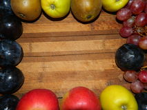 Along the perimeter of the wooden planks laid out plums, pears, apples, grapes Royalty Free Stock Photo