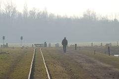 Along the railroad track. Men walking along the railroad track alone stock photography