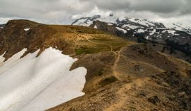 Along the Ridgeline. A aingle trail leading along a mountain ridgeline, surrounded by snow and a cloudy alpine landscape Royalty Free Stock Image