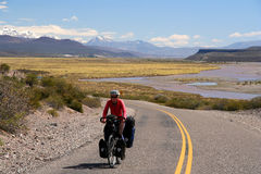 Along Rio Grande. Woman cycling on the famous national Ruta 40 ( quarenta ) in the remote part of central Argentina Stock Images