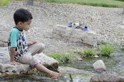 Along the river 4. A boy  looking at and playing along the river Royalty Free Stock Images