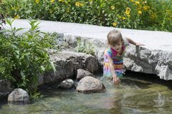 Along the river 6. A girl looking at and wading in the river Royalty Free Stock Photos