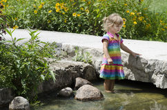 Along the river  9. A girl looking at and wading in the river Royalty Free Stock Photography