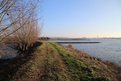 Along river Rhine named Nederrijn in autumn sun located at the town of Elst. Along river Rhine named Nederrijn in autumn sun located at the town of Elst stock photo