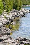 Along the rocky coast of Georgian Bay. Rocky coastline with evergreen trees lining the water's edge, in the Bruce Peninsula, on Georgian Bay, Ontario Stock Photo