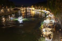 Along the Tiber River in Rome`s summer nightlife. Rome, Italy - July 30, 2017: In the scene the protagonists are the people who stroll down to the river and Royalty Free Stock Photo
